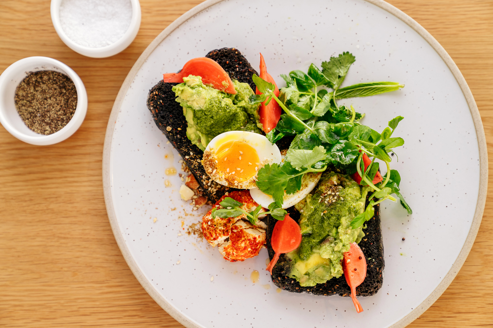 Avocado and soft boiled eggs on toast, surrouded with garnishes