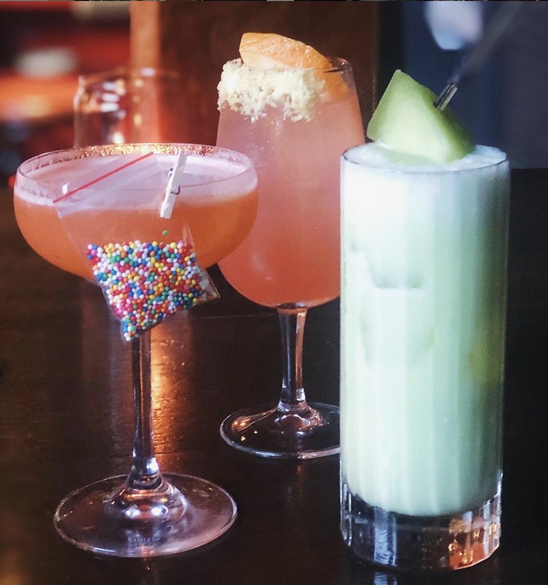 Three colourful cocktails in all different glass shapes, garnished with fruits and sprinkles