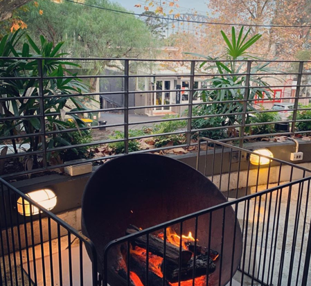 A fenced off fire pit with the Sydney Harbour Bridge in the background