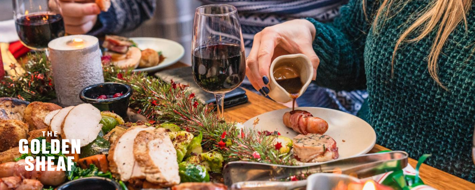 Table filled with Christmas decorations, red wine and a roast dinner feast