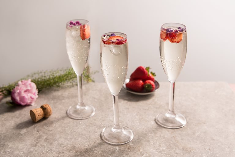 Elderflower prosecco cocktails topped with berries in flute glasses
