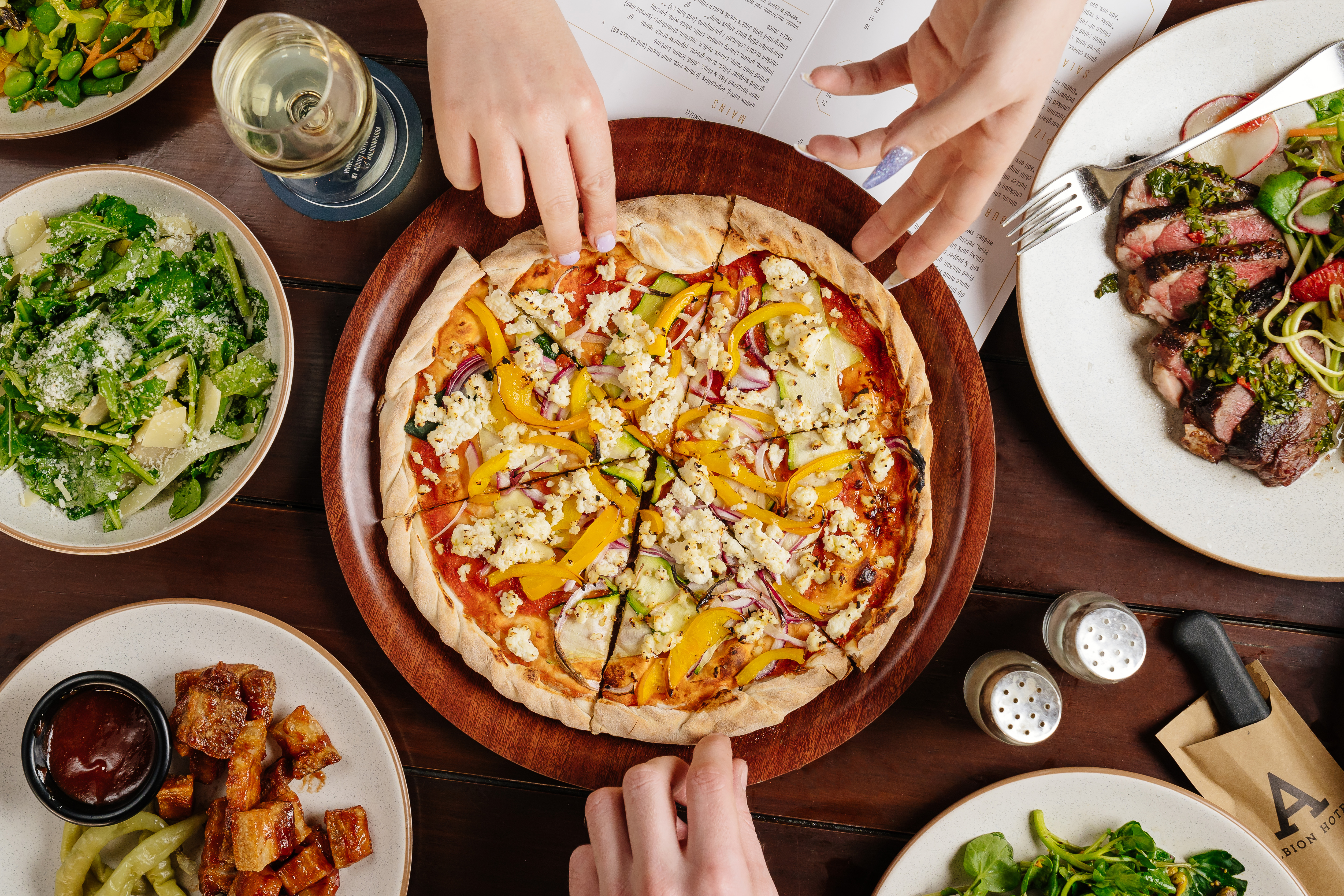 Flatlay of pizza surrounded by side dishes, with hands reaching for a slice