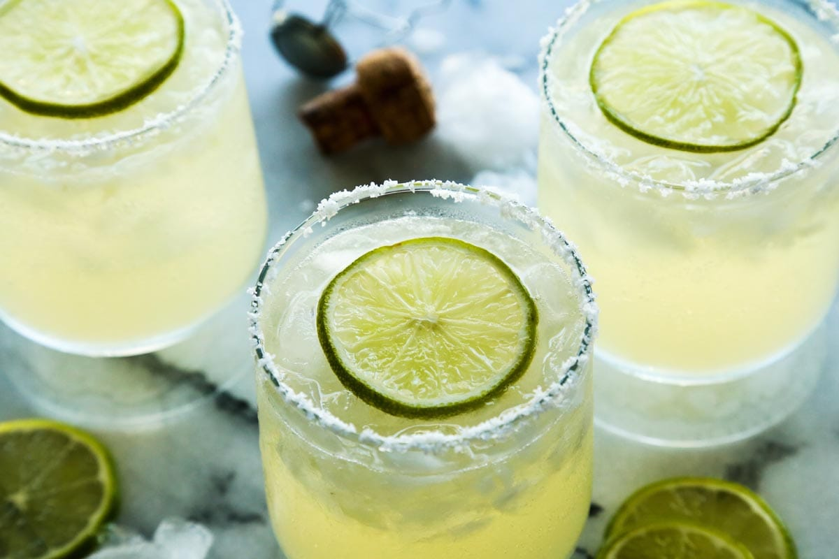 Prosecco margarita cocktail with lime wedge garnish in a salt rimmed glass