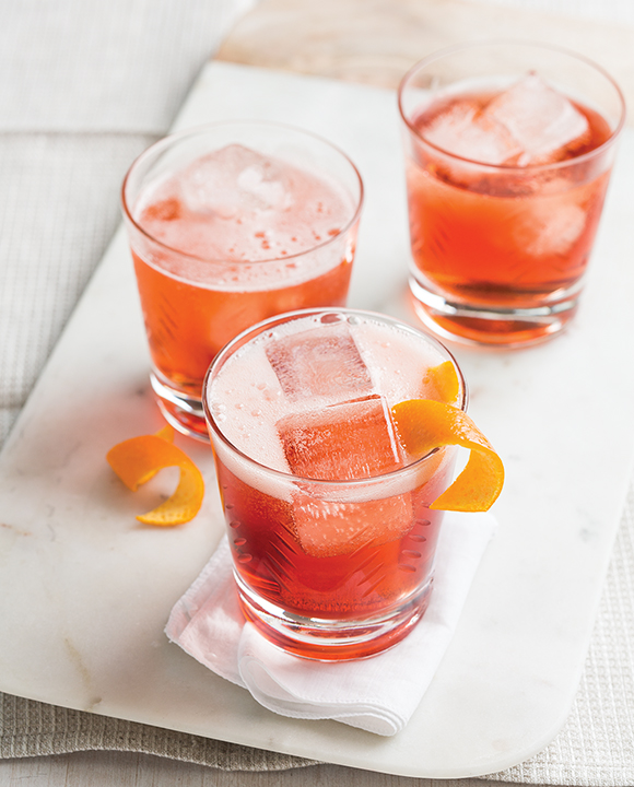 Negroni Sbagliato cocktails topped with orange wheel garnish and ice cubes